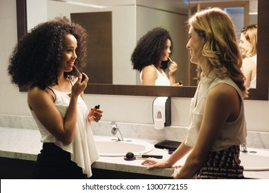 Business people in bathrooms. Young female coworkers as friends using restrooms. Toilets in office building with beautiful women talking gossip while making-up