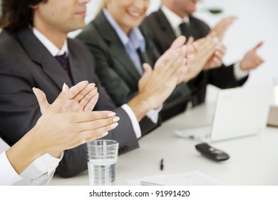 business people at a board meeting, clapping