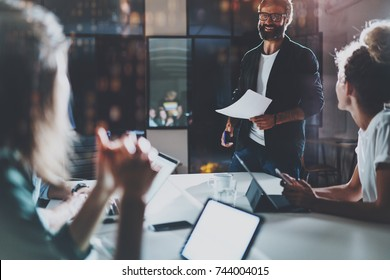 Business people brainstorming concept photo.Coworkers working at night office.Horizontal, flares effect.Blurred background