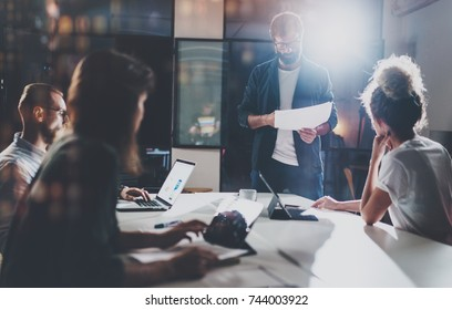 Business people brainstorming concept.Young coworkers working at night office.Horizontal, flares effect.Blurred background.Cropped