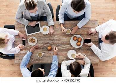 business, people, break and team work concept - close up of creative team meeting and drinking coffee with muffins during lunch in office