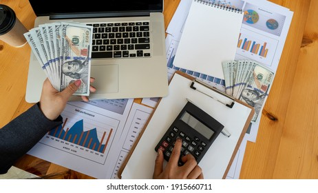 Business people are calculating company earnings with calculator with laptop and graph on top view table