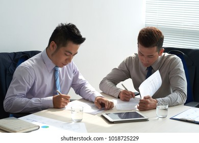 Business people carefully reading agreements before signing it