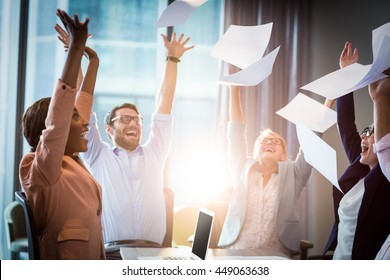 Business people celebrating by throwing papers in the air