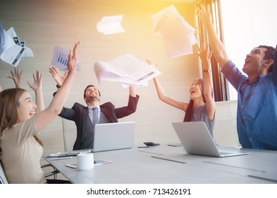business people celebrating by throwing documents after working success in office.