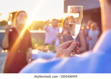 Business people celebrating success while raising champagne glasses together at rooftop party with yellow lens flare in background