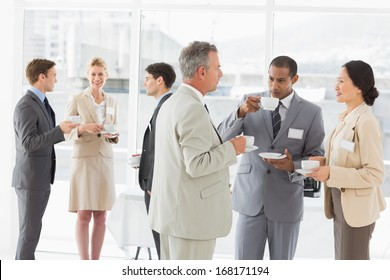 Business people chatting and drinking coffee at a conference in the office