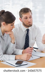 Business people chatting over documents at desk in office