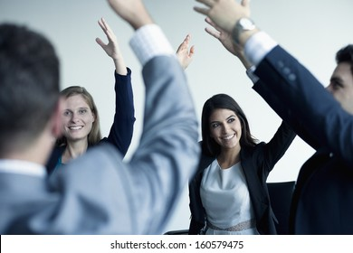 Business people cheering with arms in the air