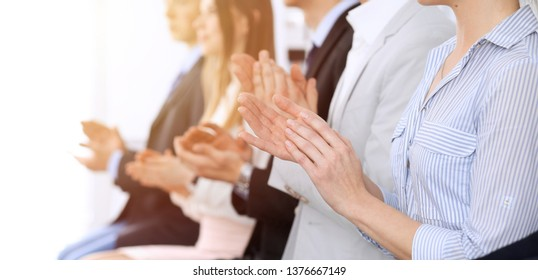 Business people clapping and applause at meeting or conference, close-up of hands. Group of unknown businessmen and women in modern white office. Success teamwork or corporate coaching concept