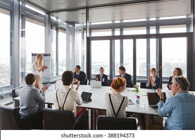 Los empresarios aplauden tras una reunión exitosa en la oficina moderna.