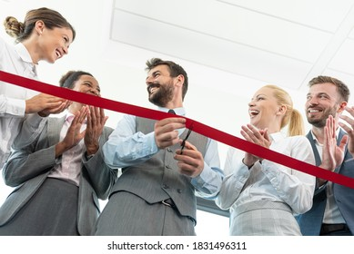 Business people clapping hands while businessman is cutting red ribbon at new office