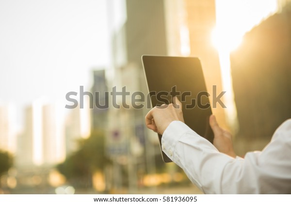 business people click his tablet during sunset in front of modern building