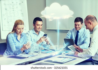 business, people, cloud computing and technology concept - smiling business team with smartphones, tablet pc computers working in office