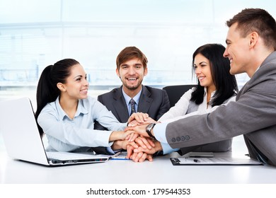 Business people collaboration team at office meeting, group smile businesspeople leader hold pile of hands putting on top of each other on desk, concept of colleagues working together cooperation
