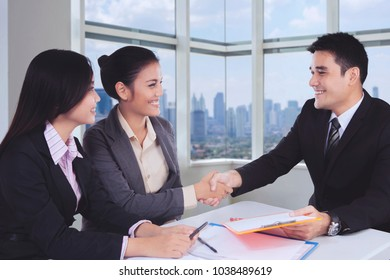Business people come to an agreement shaking hands in a meeting