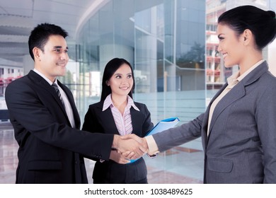 Business people come to an agreement shaking hands at modern office