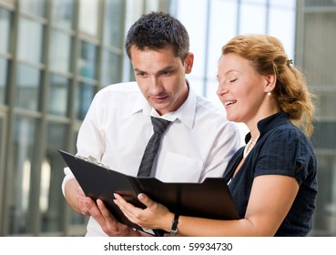 Business people communicating in front of office building and trying to sign the contract between two companies. Red-haired woman smiling and showing documents to his partner.
