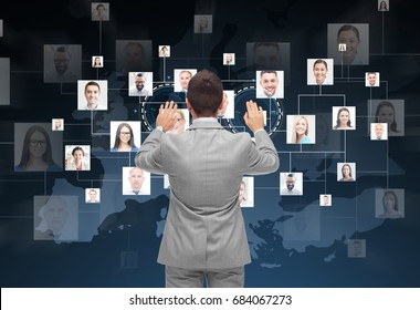 business, people, communication, cooperation and technology concept - businessman touching virtual screen with contacts icons and europe map over dark blue background