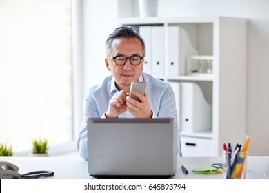 business, people, communication and technology concept - businessman with laptop computer texting on smartphone at office
