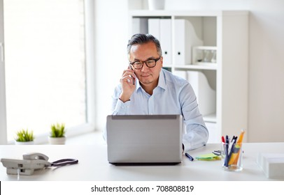 business, people, communication and technology concept - businessman with laptop computer calling on smartphone at office