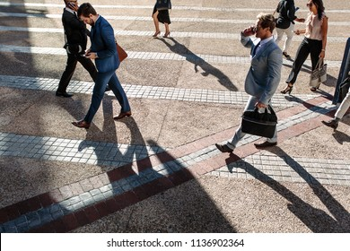 Business people commuting to office in the morning carrying office bags and using mobile phones.
