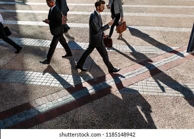 Business people commuting to office in the morning carrying office bags and using mobile phones. Businessmen in a hurry to reach office walking on city street using their mobile phone.