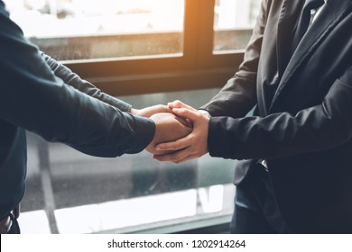 Business people compassionately holding hands at office room.