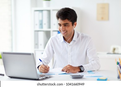 business and people concept - businessman in earphones with papers and laptop computer working at office and listening to music