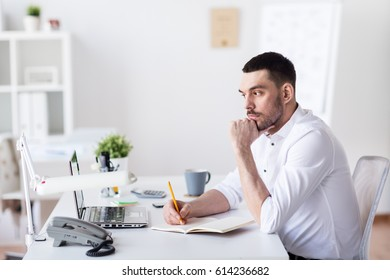 business and people concept - businessman with laptop and notebook sitting at office table and thinking