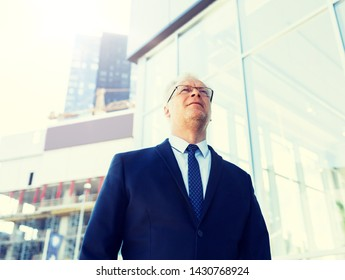 business and people concept - senior businessman on city street