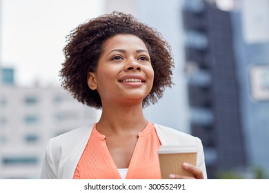 business and people concept - young smiling african american businesswoman with coffee cup in city