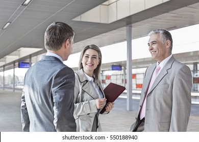 Business people conversing on train platform
