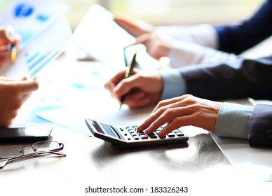 Business people counting on calculator sitting at the table. Close up of hands and stationery