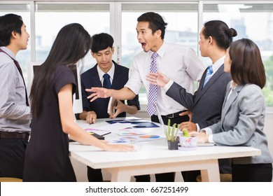 Business, People, Crisis and Confrontation concept - Asian businessman behaves insultingly impolitely at meeting and businesspeople arguing furious in office.