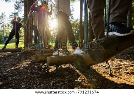 Business People Crossing Swinging Logs In Forest