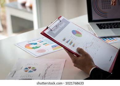 business people discuss meeting targets, sitting at the business table with documents. hand pointing at business document during discussion at meeting.