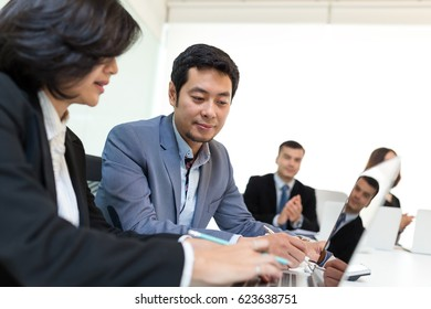 Business people discuss on laptop computer