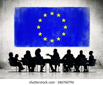 Business People Discussing Around The Conference Table And A Flag Of European Union