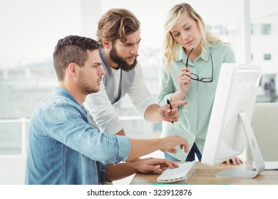 Business people discussing by computer while at desk in office