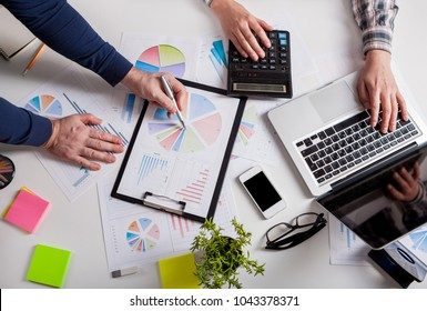 Business people discussing the charts and graphs showing the results of their successful teamwork.  Stock market chart and finger pointing on tablet in office.