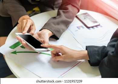 business people discussing the charts and graphs showing the results of their successful by smart phone