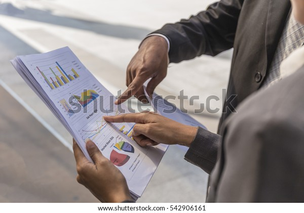 Business people discussing the charts and graphs showing the results of their successful teamwork,Businessman,engineer pointing at document while discussing it with colleague,outside the premises,