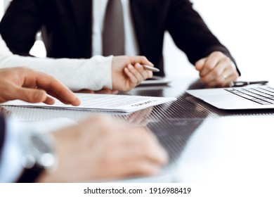 Business people discussing contract working together at meeting in modern office. Unknown businessman and woman with colleagues or lawyers at negotiation