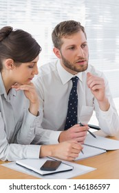 Business people discussing documents at desk in office