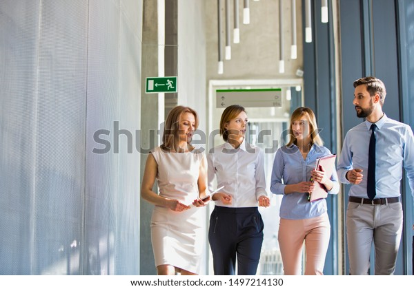 Business people discussing plans while walking in office hall