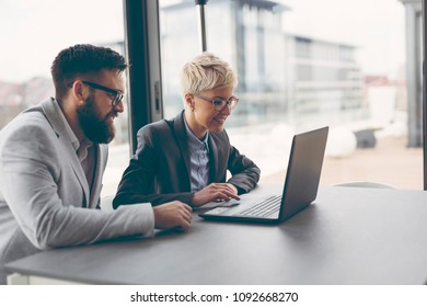 Business people discussing work related matters, working on a laptop computer. Focus on the woman