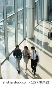 Business people in discussion walking together through office lobby