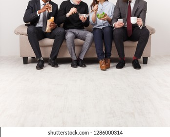 Business people eating, talking and smiling while having lunch sitting on couch in modern office, copy space