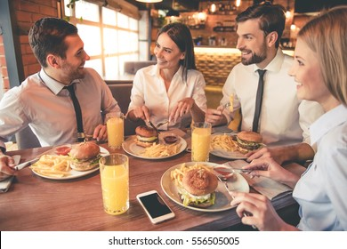 Business people are eating, talking and smiling while having lunch in cafe